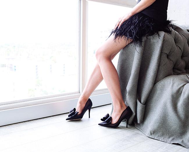 zapatos negro con lazo en una modelo apoyada en un sofa