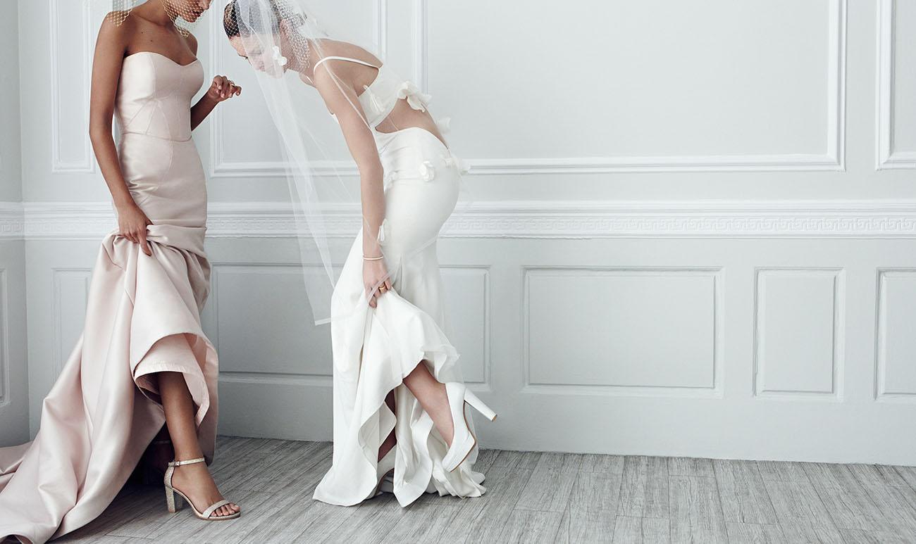 dos modelos vestidas de novia enseñandose los zapatos